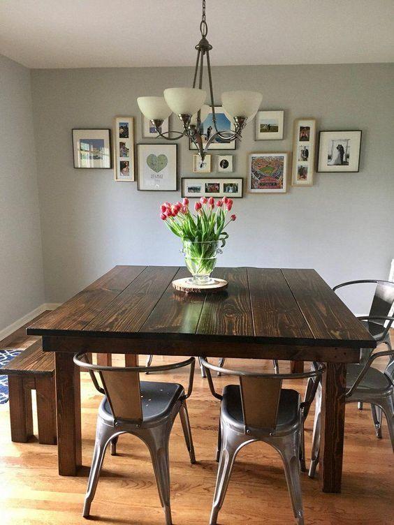 Mesa de jantar quadrada com bancos, cadeiras pratas, quadros e vaso de flores.