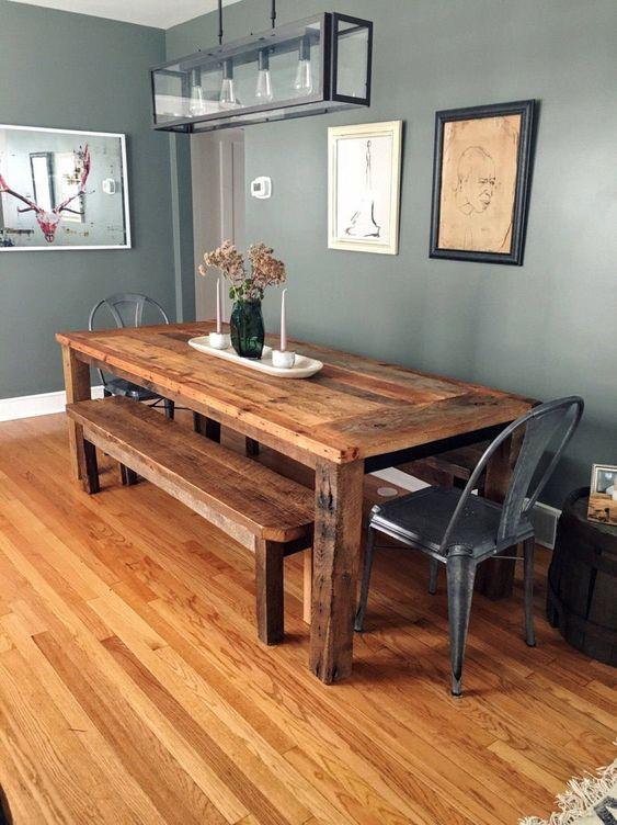 Sala de jantar com mesa de madeira, bancos e cadeiras.