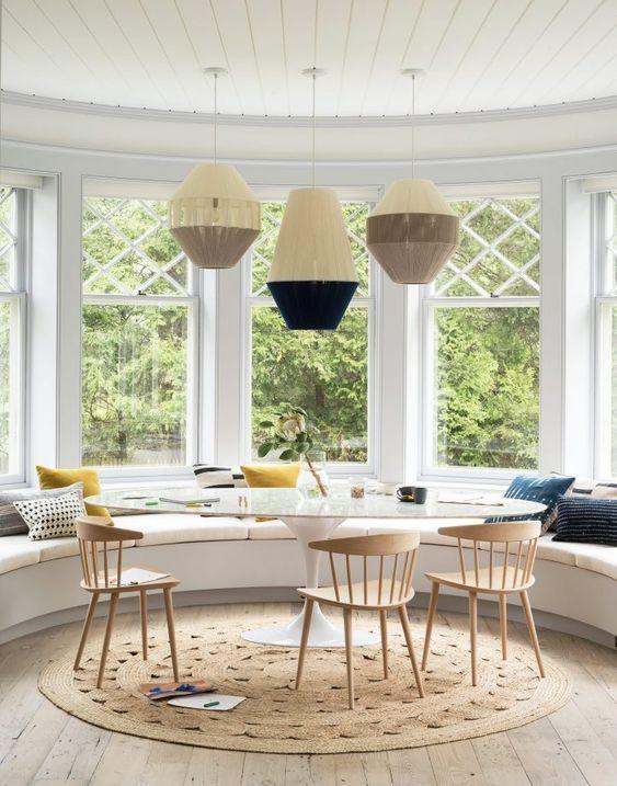 Três lustre em cima de uma mesa de jantar oval que fica em frente um sofá.