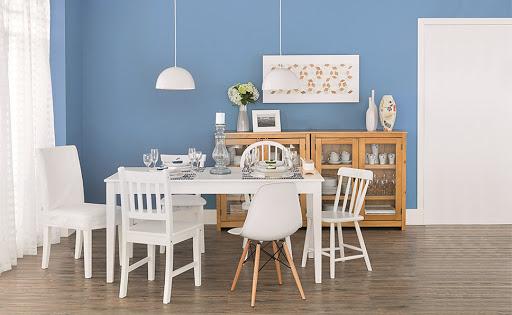 Sala de jantar com parede azul, cristaleira e mesa com cadeiras brancas.