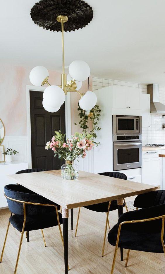 Lustre com base preta e bolas brancas no centro da mesa de jantar.