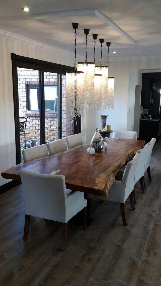 Sala de jantar decorada com cinco lustres de correntes com pedrarias.