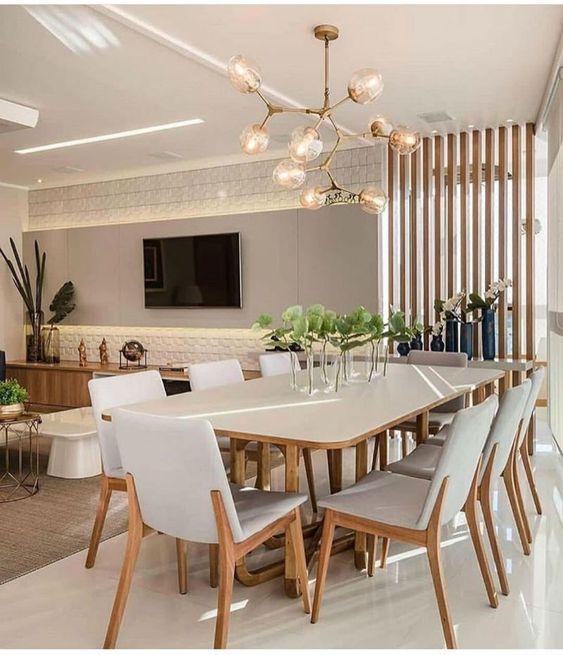 Sala de jantar com mesa de oito cadeiras e lustre dourado.