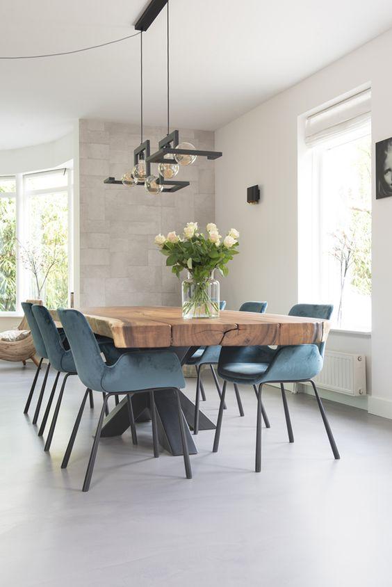 Sala de jantar com mesa de madeira, cadeiras azuis e lustre preto.