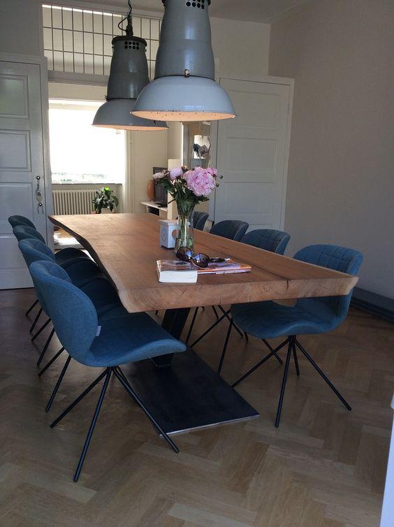 Sala de jantar decorada com dois lustres grandes azuis e um vaso de plantas roxas na mesa.