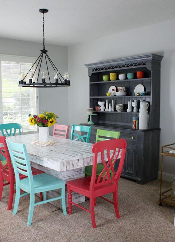Mesa branca de madeira e cadeiras azuis, vermelhas, verdes e rosa.