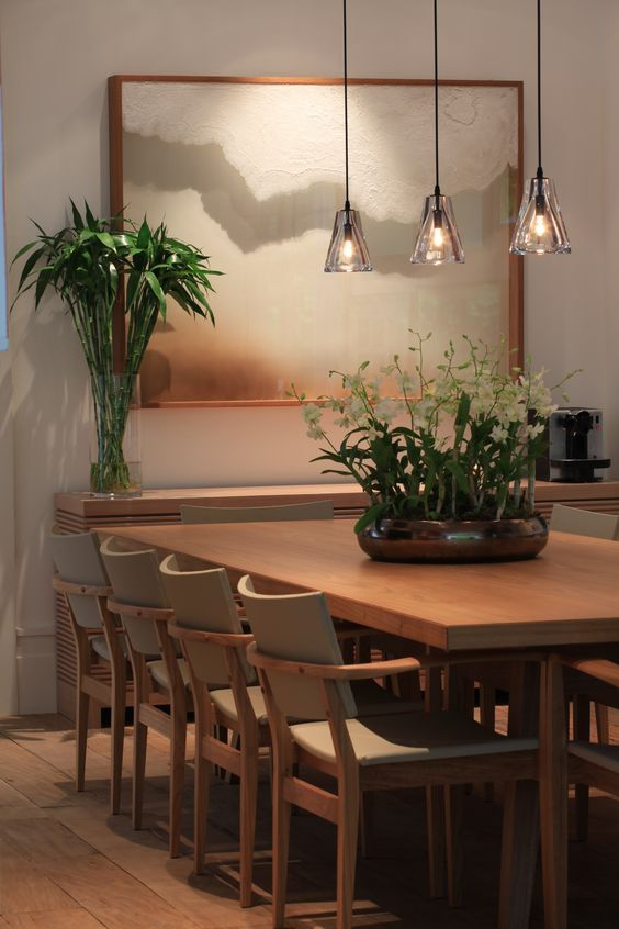 Sala com mesa de madeira e cadeiras nudes.