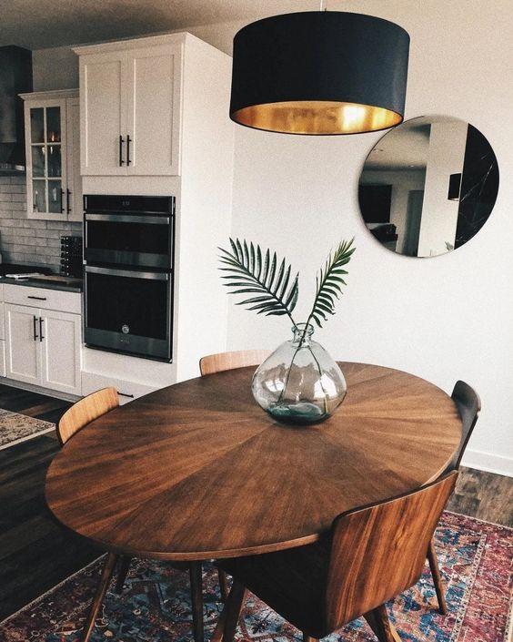 Sala de jantar decorada com espelho redondo e lustre no mesmo formato.