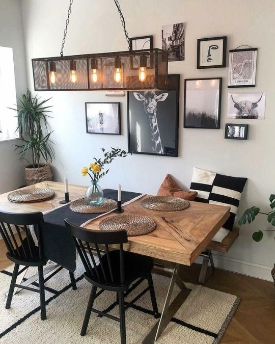 Decoração de slaa de jantar com quadros, almofadas, lantas e lustre.