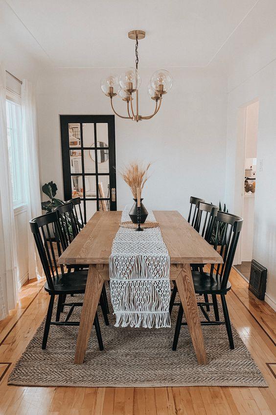 Sala de jantar pequena com mesa de madeira e cadeiras pretas.