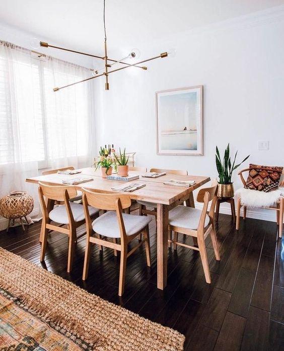 Sala de jantar decorada com quadro, lustre e plantas.