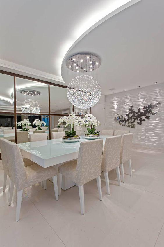 Grande lustre redondo de cristas em cima da mesa de jantar.