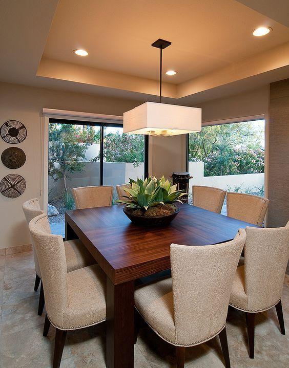 Sala de jantar decorada com lustre quadrado no mesmo formato que a mesa.