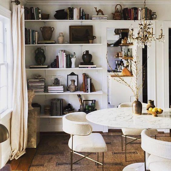 Sala de jantar decorada com prateleiras e vários artigos decorativos.