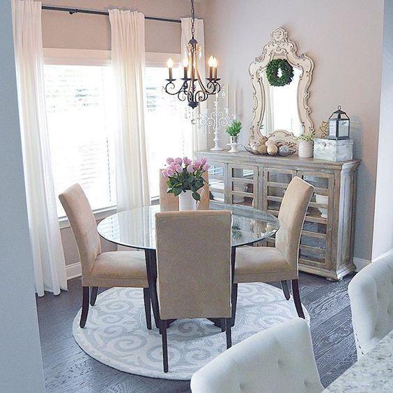 Sala de jantar decorada com espelho, cristaleira e lustre.