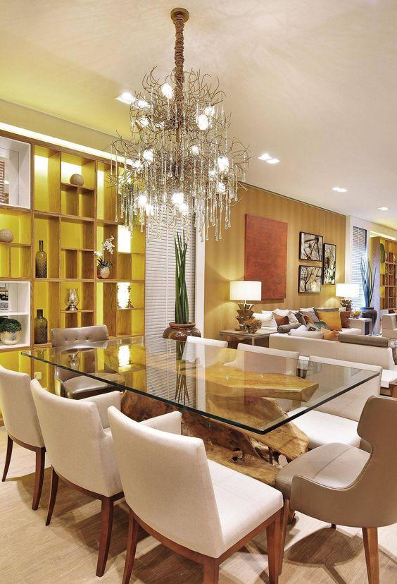 Sala de jantar decorada com mesa de vidro e pé de madeira.