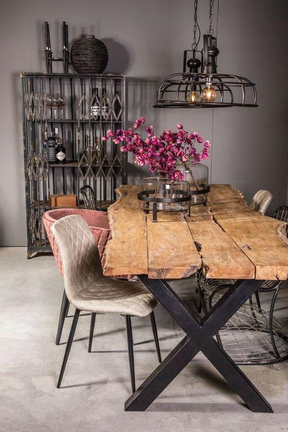 """Sala de jantar exótica com mesa rústica de madeira com pés em """"X""""."""