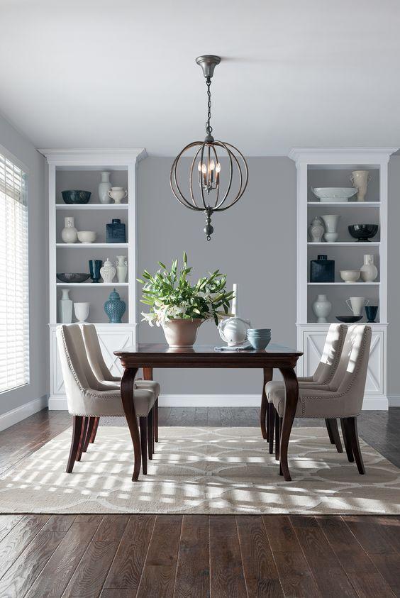 Dois móveis com louças, lustre e plantas decorando a sala de jantar.