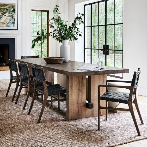 Sala de jantar bem iluminada com lareira, quadro e vaso de plantas.