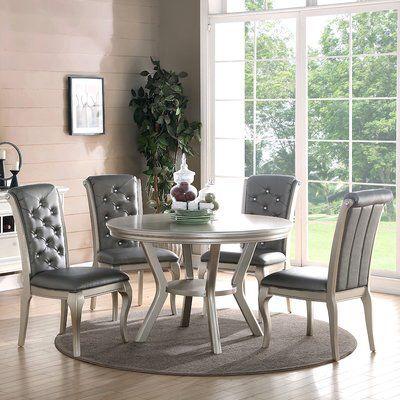 Sala de jantar decorada com mesa redonda e cadeiras estofadas cinzas.