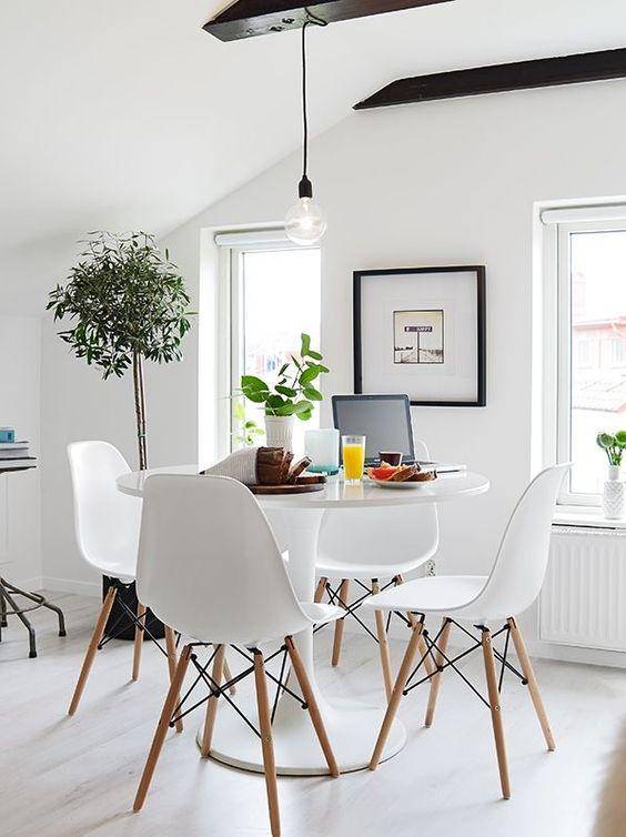 Sala de jantar branca decorada com quadro e vasos de plantas.