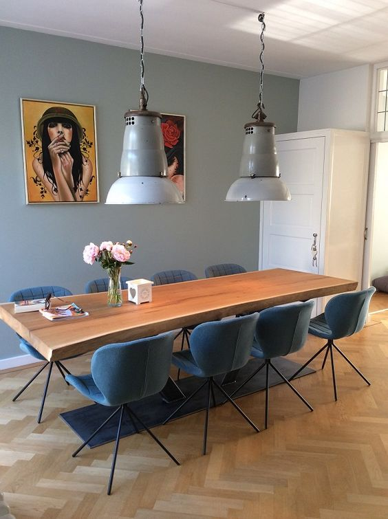 Sala de jantar com decoração azul e quadros coloridos.