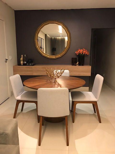 Sala de jantar decorada pequena com mesa redonda de madeira e espelho.