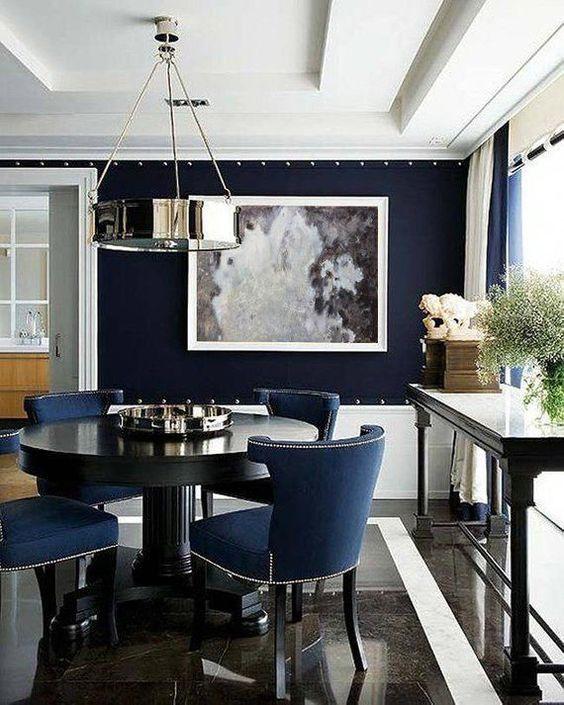 Sala de jantar decorada em azul, preto e branco.