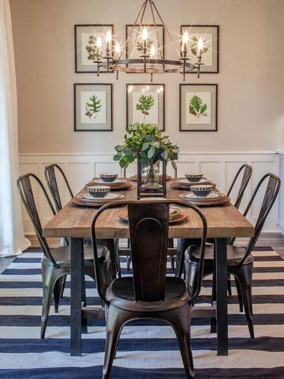 Sala de jantar decorada com lustre, quadros e vaso de planta.