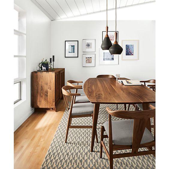 Sala de jantar com paredes brancas e móveis de madeira.