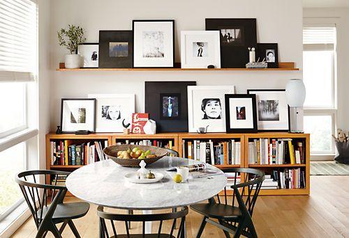Sala de jantar decorada com quadros pretos e brancos.
