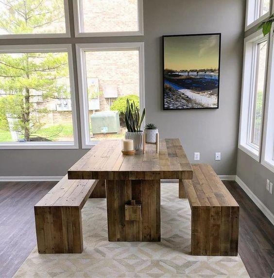 Mesa de madeira com bancos no canto do cômodo.