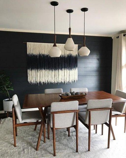 Sala de jantar decorada com três lustres e quadro feito de linhas.