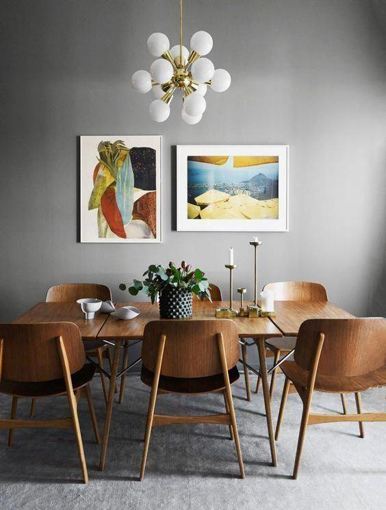 Parede cinza com dois quadros coloridos, um abstrato e outro de paisagem.