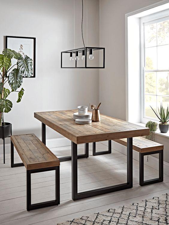 Mesa e bancos de madeira com pés vazados pretos de ferro.