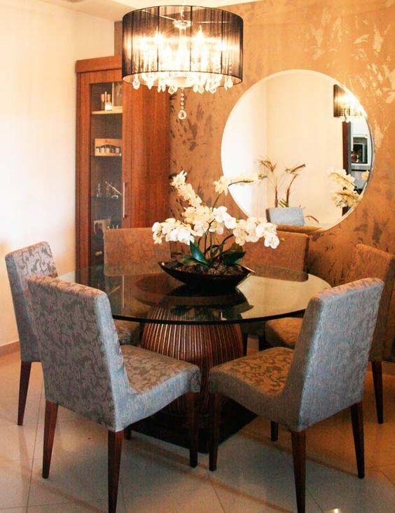 Sala de jantar com cristaleira, espelho, vaso de flores e lustre.