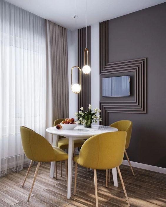 Sala de jantar com mesa branca redonda e cadeiras amarelas.