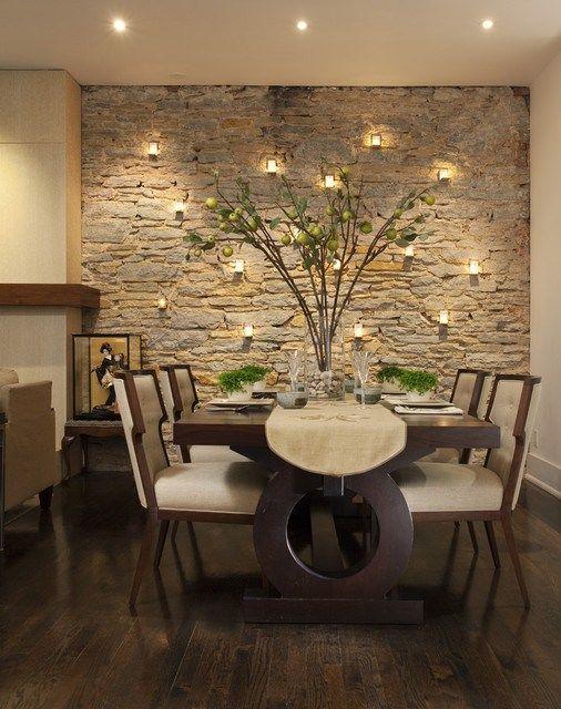Sala de jantar decorada com parede revestida de pedras e vários pontos de luz.