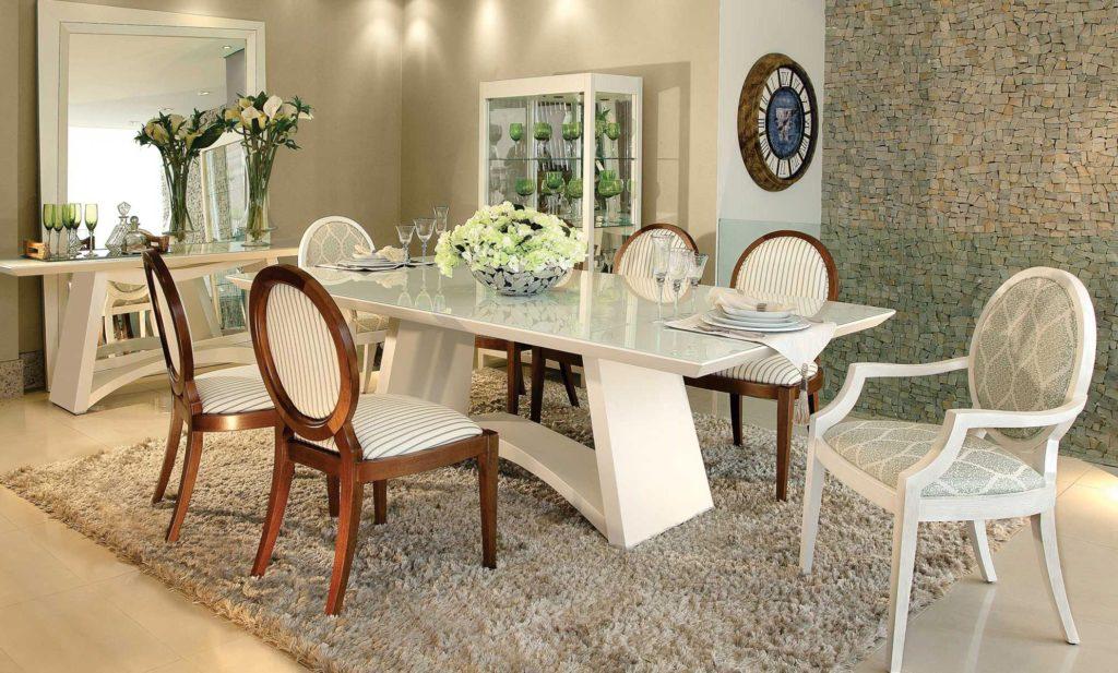 Sala de jantar espaçosa com dois tipos de cadeiras.