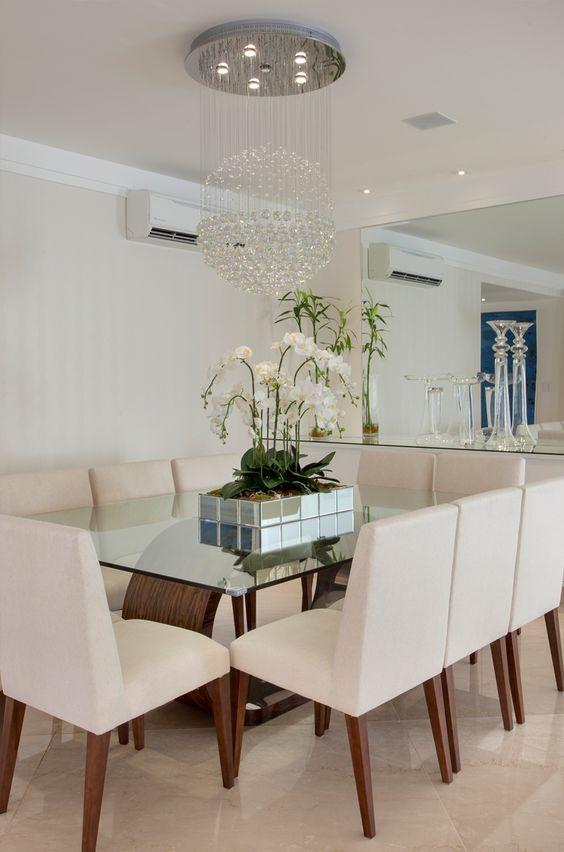 sala de jantar integrada branca com lustre de cristal.