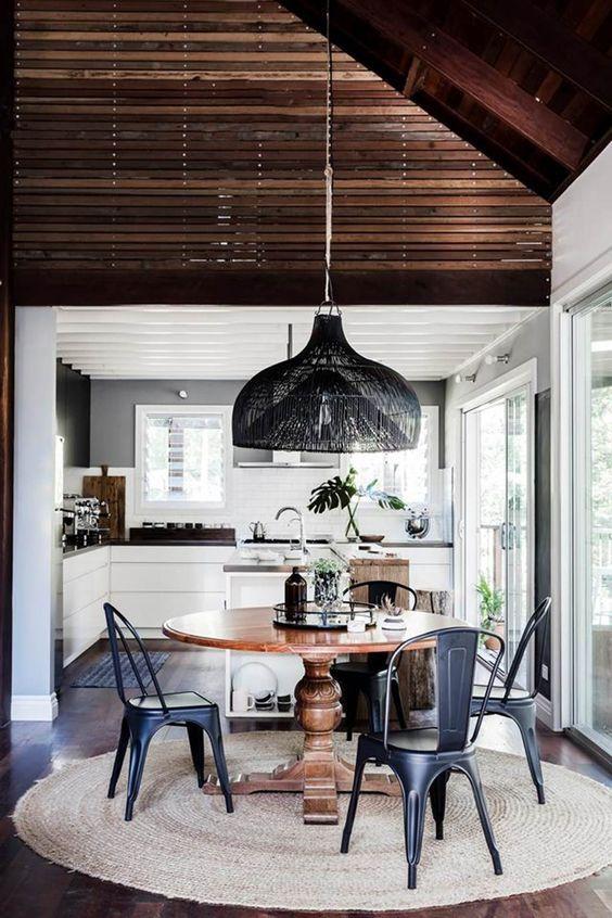 sala de jantar cm cozinha e lustre preto.