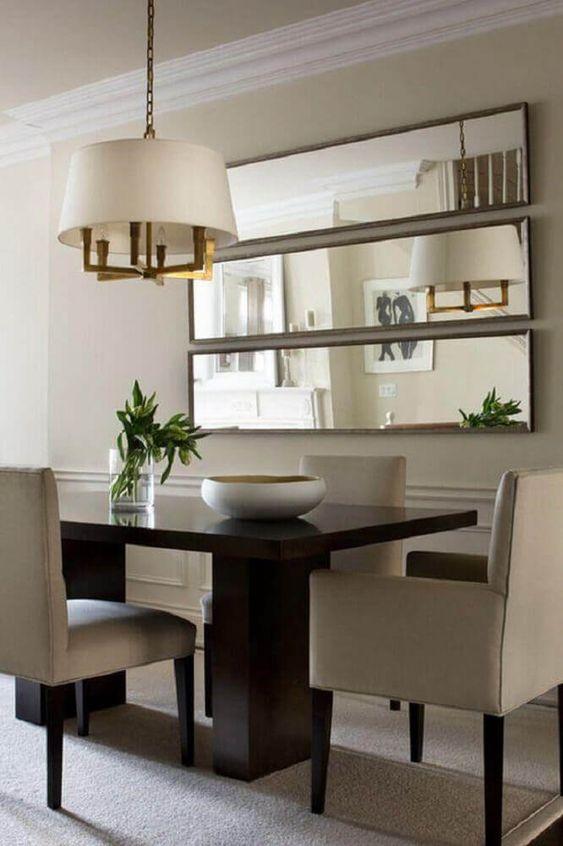 mesa com espelhos atrás e lustre dourado com branco