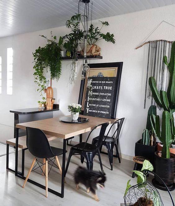sala de jantar pequena preta e com plantas.