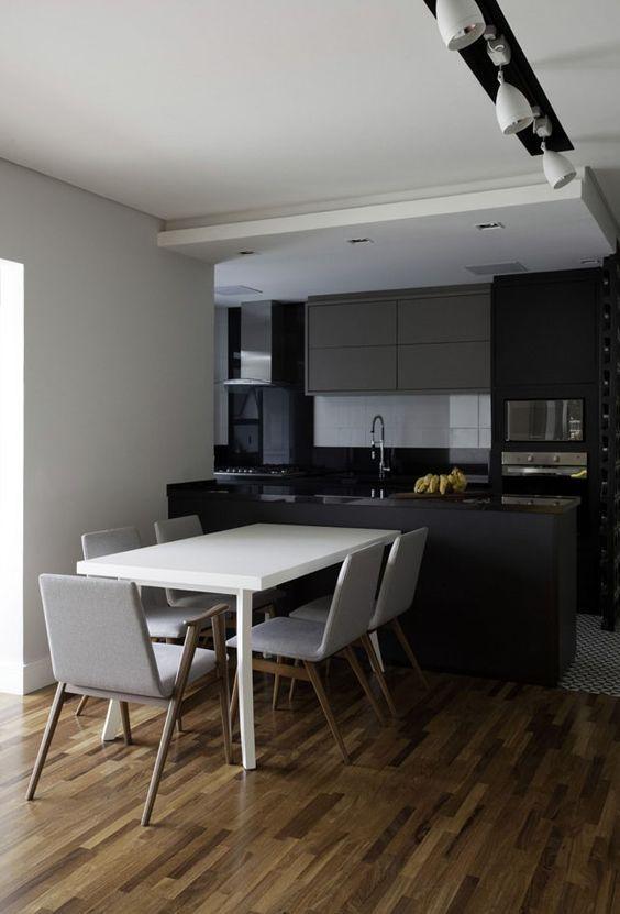 sala de jantar com piso de madeira e spot de iluminação.