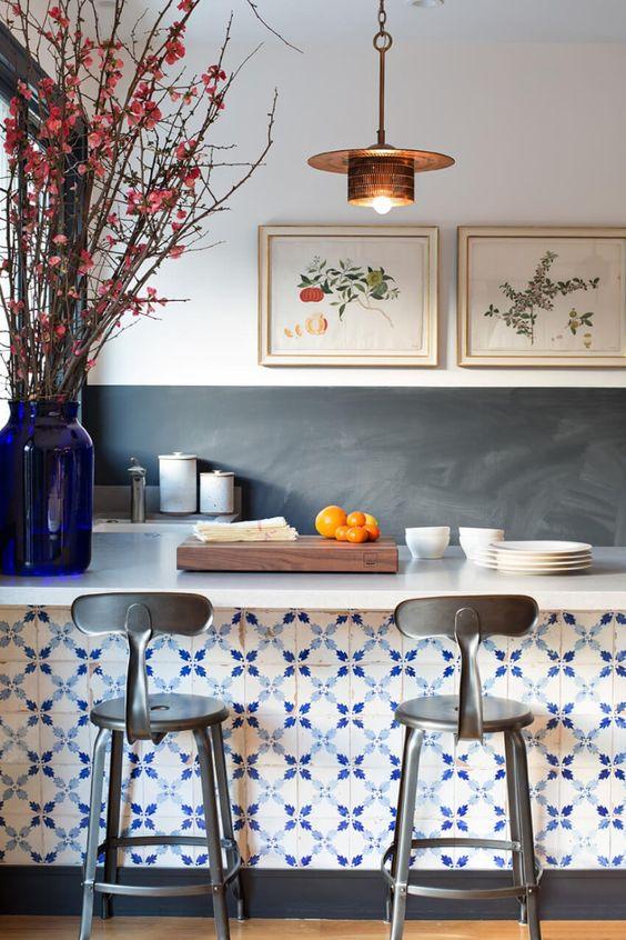 Cozinha americana com bancada revestida com azulejo português.