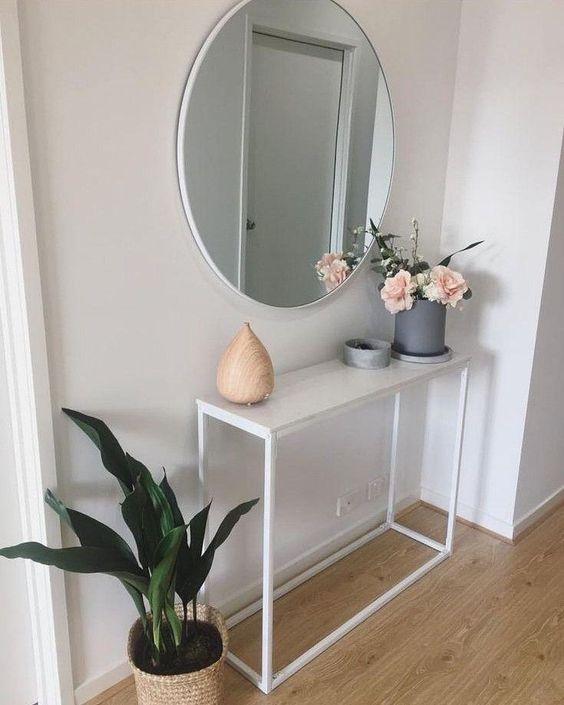 hall de entrada com aparador branco simples e espelho redondo