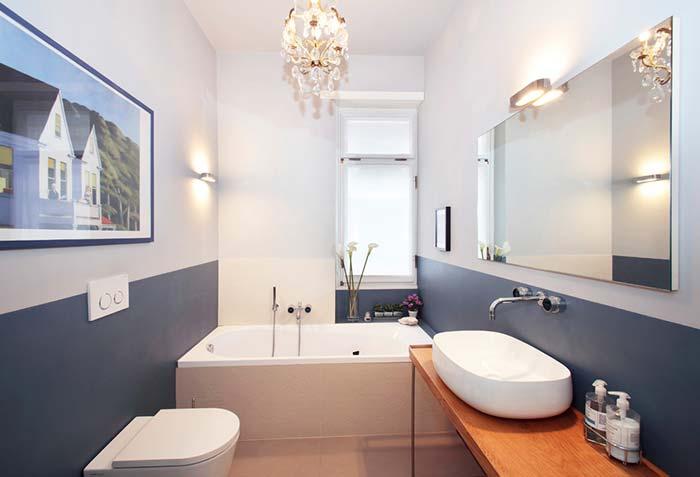 banheiro azul e branco com lustre e misturador