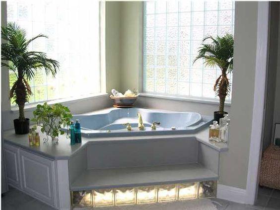 banheira de canto com blocos de vidro.
