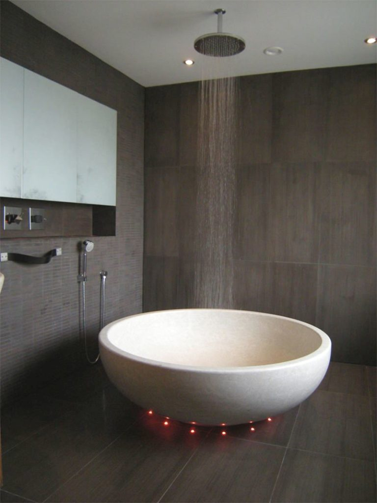 banheiro com banheira redonda e chuveiro de teto