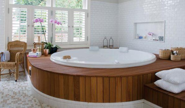 banheira redonda com dek de madeira e azulejos brancos